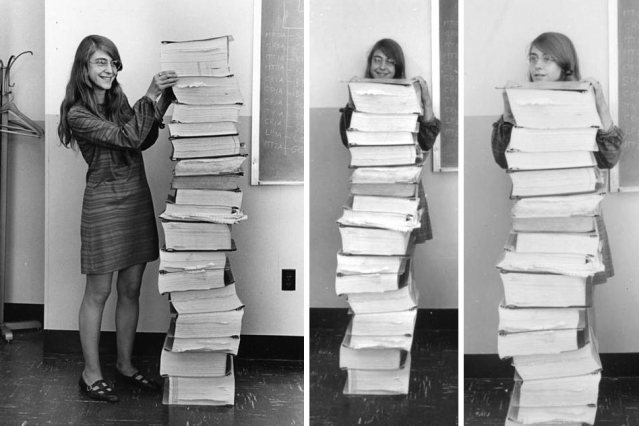 Margaret Hamilton standing next to the code that sent astronauts to the moon.