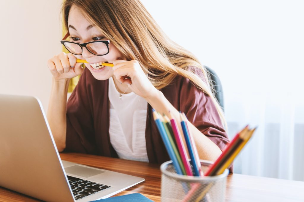 woman at computer biting a pencil