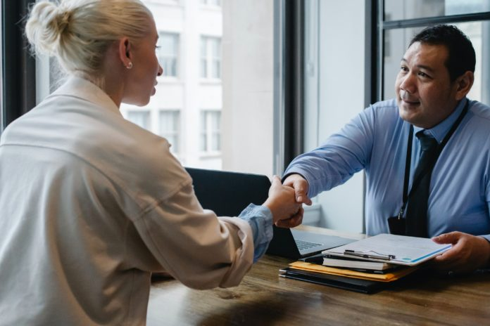woman shaking hands with a man while sitting across from each other at a desk