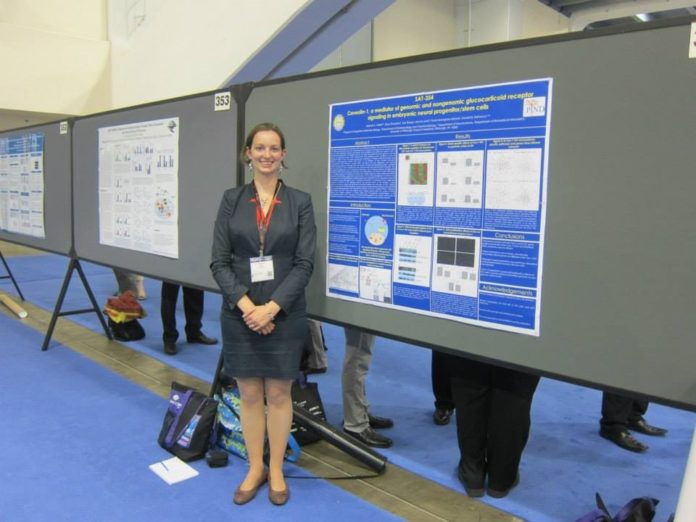 Melanie (the author) in a suit at a conference standing in front of her scientific poster